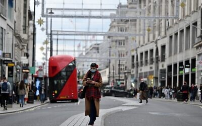 A woman wearing a protective face covering checks her phone as she walks down Oxford Street in London on October 17, 2020, as Londoners face more stringent novel coronavirus COVID-19 restrictions as the number of cases rises. (Justin Tallis/AFP)