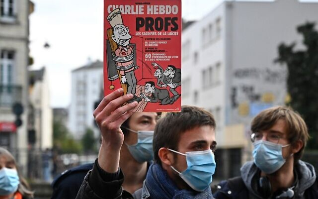A man holds a Charlie Hebdo cover during a demonstration in Rennes on October 17, 2020, a day after a teacher was beheaded in Conflans-Sainte-Honorine, 30kms northwest of Paris, in an alleged Islamist terror attack. (Damien Meyer/AFP)