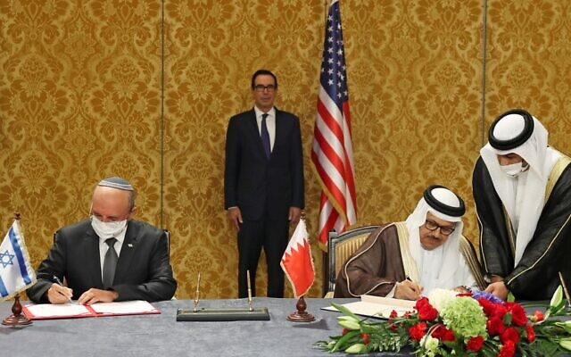 The head of the Israeli delegation, National Security Advisor Meir Ben Shabbat (L), and Bahraini Foreign Minister Abdullatif bin Rashid Al-Zayani, sign the Israel-Bahrain accord formalizing diplomatic relations, in the Bahraini capital Manama, on October 18, 2020. US Treasury Secretary Steve Mnuchin (C) looks on. (RONEN ZVULUN / POOL / AFP)