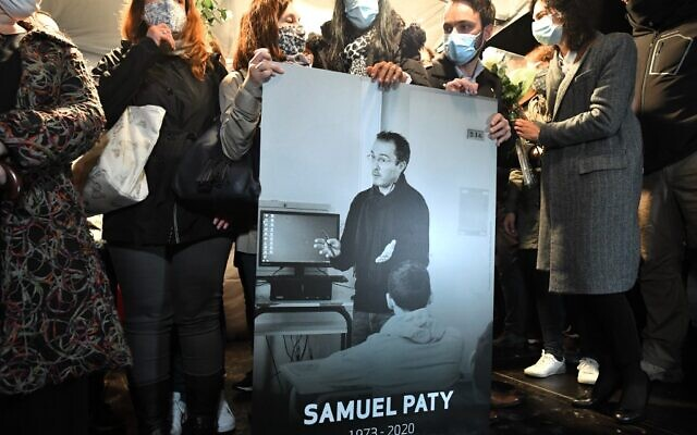 Relatives and colleagues hold a picture of Samuel Paty during the 'Marche Blanche' in Conflans-Sainte-Honorine, northwest of Paris, on October 20, 2020, in solidarity after a teacher was beheaded for showing pupils cartoons of the Prophet Muhammad. (Photo by Bertrand GUAY / AFP)