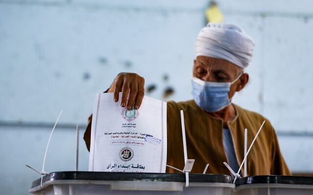 A man, mask-clad due to the COVID-19 coronavirus pandemic, casts his vote at a polling station in the Talibeya district of Giza, the twin-city of Egypt's capital, on October 24, 2020, while voting in the first stage of the lower house elections. (Khaled DESOUKI / AFP)