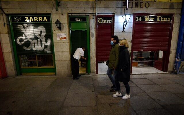 A couple walk past a bar at the end of a day's work at Plaza Mayor in Madrid on October 24, 2020. (Photo by OSCAR DEL POZO / AFP)