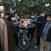 Iranians burn a picture of French President Emmanuel Macron and Prime Minister Benjamin Netanyahu during a protest outside the French embassy in Tehran against comments by Macron defending cartoons of the Prophet Mohammed, on October 28, 2020 (ATTA KENARE / AFP)