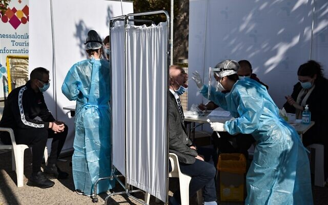 People are tested for COVID-19 by medical staff in the waterfront of Thessaloniki on October 29, 2020. (Sakis MITROLIDIS / AFP)
