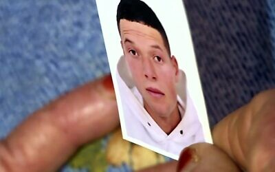 This image grab from AFP TV shows a picture of Nice assailant Brahim Issaoui, who a day earlier killed three people and wounded several others in the southern French city of Nice, held by his mother at the family home in the Tunisian city of Sfax, on October 30, 2020. (AFPTV teams / AFP)