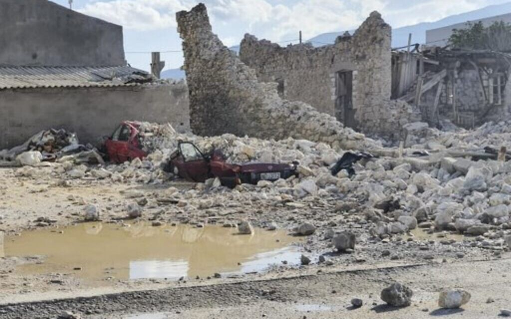 This picture shows destroyed car and collapsed buildings after an earthquake in the island of Samos on October 30, 2020.  (Photo by STR / Eurokinissi / AFP)