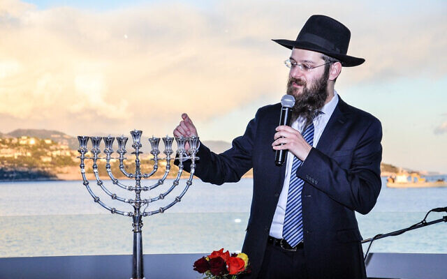 Rabbi Tanhoum Matusof lights a Hanukkah candle at a hotel in Monaco, December 25, 2016. (Courtesy of the Jewish Cultural Center of Monaco/ via JTA)