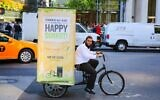 File: A Chabad emissary transports a mobile sukkah through New York City on a bicycle in 2014 (Courtesy of Chabad.org)
