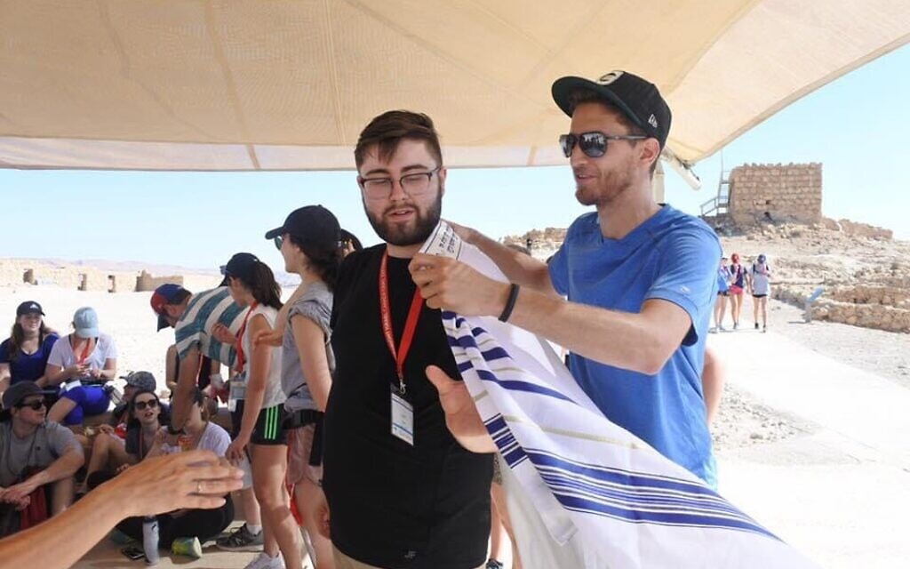 Justin Christopher Tobin, seen here wearing a tallit during a Birthright trip, says El Al agents interrogated him about his middle name ahead of his visit to Israel. (Courtesy of Tobin/ via JTA)
