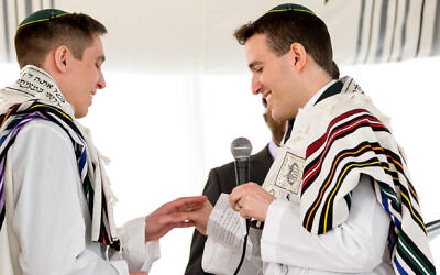 Nadiv Schorer, right, married Ariel Meiri in 2020 with Orthodox rabbi Avram Mlotek officiating. (David Perlman Photography via JTA)