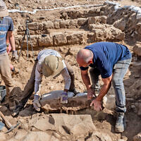 Workers lift the 3rd-century CE Roman boundary stone at Israel Antiquities Authority excavations at Nafah in the Golan Heights (Assaf Peretz/Israel Antiquities Authority)