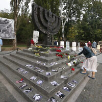 A woman lays flowers at a menorah monument close to the Babi Yar ravine where tens of thousands of Jews were killed during WWII, in Kyiv, Ukraine, September 29, 2020. (AP Photo/Efrem Lukatsky)