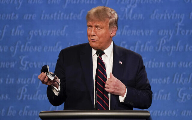 In this September 29, 2020, file photo, US President Donald Trump holds out his face mask during the first presidential debate  at Case Western University and Cleveland Clinic, in Cleveland, Ohio. (AP/Julio Cortez, File)