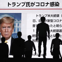People walk past a screen showing the news report that US President Donald Trump has tested positive for the coronavirus, Friday, Oct. 2, 2020, in Tokyo.  (AP Photo/Eugene Hoshiko)