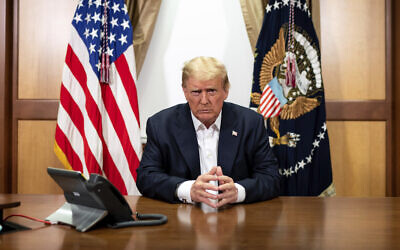 In this image provided by the White House, US President Donald Trump listens during a phone call with Vice President Mike Pence, Secretary of State Mike Pompeo, and Chairman of the Joint Chiefs of Staff Gen. Mark Milley, October 4, 2020, in his conference room at Walter Reed National Military Medical Center in Bethesda, Maryland. (Tia Dufour/The White House via AP)