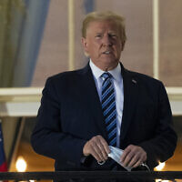 In this Monday, Oct. 5, 2020 photo, President Donald Trump removes his mask as he stands on the Blue Room Balcony upon returning to the White House in Washington, after leaving Walter Reed National Military Medical Center, in Bethesda, Md. Trump announced he tested positive for COVID-19 on Oct. 2. (AP Photo/Alex Brandon)
