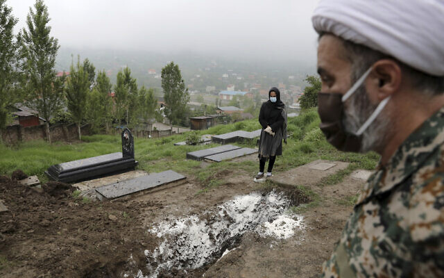 A woman wearing mask and gloves, prays at the grave of her mother who died from the coronavirus, at a cemetery in the outskirts of the city of Babol, in northern Iran, April 30, 2020. (AP Photo/Ebrahim Noroozi, File)