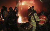 Firefighters extinguish a fire at a building  after a diesel tank exploded in the neighborhood of Tarik al-Jadida, in Beirut, Lebanon on October 9, 2020. (AP/Bilal Hussein)