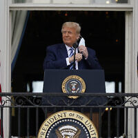 US President Donald Trump removes his face mask to speak from the Blue Room Balcony of the White House to a crowd of supporters, October 10, 2020, in Washington. (AP Photo/Alex Brandon)
