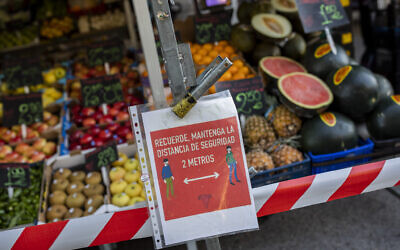 A sign of social distancing guidelines hangs on a street stall in a market in Madrid, Spain, October 13, 2020. (AP Photo/Bernat Armangue)