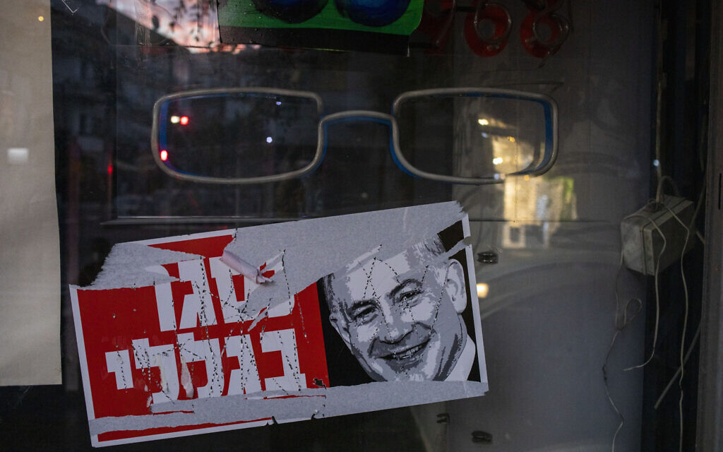 """A poster reads """"closed because of me"""" with an image of Prime Minister Benjamin Netanyahu on a closed shop in Tel Aviv, October 13, 2020. (AP Photo/Ariel Schalit)"""