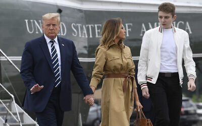 In this August 16, 2020 file photo, US President Donald Trump, first lady Melania Trump and their son, Barron Trump, walk off of Marine One and head toward Air Force One at Morristown Municipal Airport in Morristown, N.J. (AP Photo/Susan Walsh)