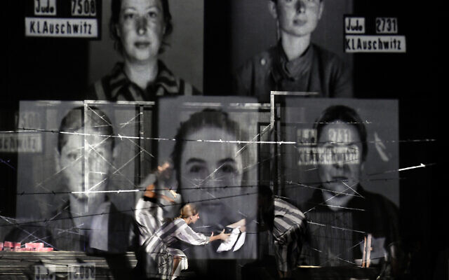 """Portraits of Auschwitz death camp prisoners are displayed on a mesh as actresses of the Jewish State Theater perform during the premiere of the """"The Beautiful Days of My Youth"""" play, based on the diary of Romanian Jewish Holocaust survivor Ana Novac, in Bucharest, October 16, 2020. (AP Photo/Andreea Alexandru)"""