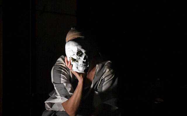 """Luana Stoica of the Jewish State Theater performs, wearing a face masks for protection against COVID-19 infection, during the rehearsals for the premiere of the """"The Beautiful Days of My Youth"""" play, based on the diary of Romanian Jewish Holocaust survivor Ana Novac, in Bucharest, October 15, 2020. (AP Photo/Andreea Alexandru)"""