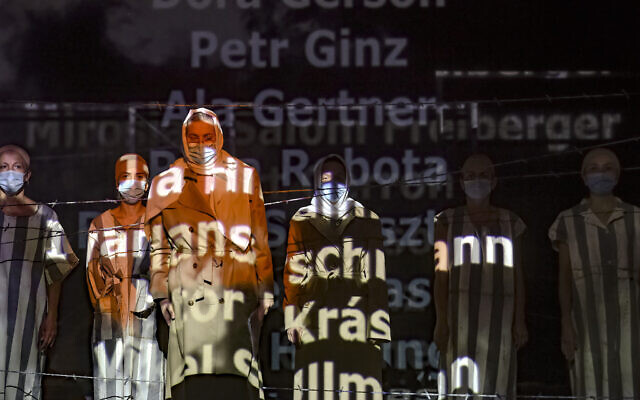 """Names of victims scroll on a mesh at the Jewish State Theater as actresses perform wearing face masks for protection against COVID-19 infection, during the rehearsals for premiere of the """"The Beautiful Days of My Youth"""" play, based on the diary of Romanian Jewish Holocaust survivor Ana Novac, in Bucharest, October 15, 2020. (AP Photo/Andreea Alexandru)"""