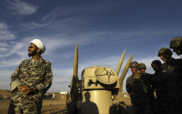An Iranian clergyman stands next to missiles and army troops, during a maneuver, in an undisclosed location in Iran, November 13, 2012. (Majid Asgaripour/ Mehr News Agency via AP/ File)