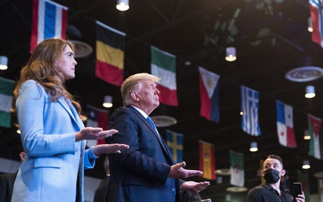 US President Donald Trump closes his eyes as he accepts blessings as he attends church at International Church of Las Vegas, Sunday, Oct. 18, 2020, in Las Vegas, Nev. Counselor to the President Hope Hicks is at left. (AP Photo/Alex Brandon)