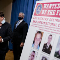 A poster showing six wanted Russian military intelligence officers is displayed as Assistant Attorney General for the National Security Division John Demers, left, takes the podium to speak at a news conference at the Department of Justice, Monday, Oct. 19, 2020, in Washington. Also pictured is US Attorney for the Western District of Pennsylvania Scott Brady, center. (AP Photo/Andrew Harnik, pool)