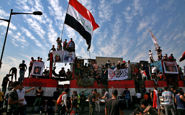 Anti-government protesters gather on the closed Joumhouriya Bridge that leads to the Green Zone government areas in Baghdad, Iraq, October 25, 2020. (AP Photo/Khalid Mohammed)
