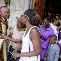 In this Sunday, June 2, 2019, file photo, Washington DC Archbishop Wilton Gregory, left, greets parishioners following Mass at St. Augustine Church in Washington. Pope Francis has  named 13 new cardinals, including Washington DC Archbishop Wilton Gregory, who would become the first Black US prelate to earn the coveted red cap.  (AP Photo/Andrew Harnik)