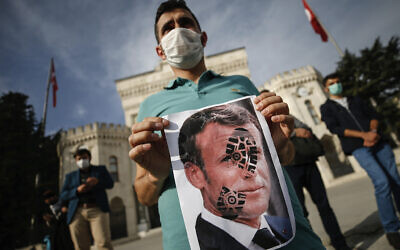 A man holds a photograph of France's President Emmanuel Macron, stamped with a shoe mark, during a protest against France in Istanbul, October 25, 2020. (AP Photo/Emrah Gurel)