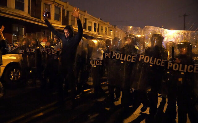 Sharif Proctor lifts his hands up in front of a police line during a protest in response to the police shooting of Walter Wallace Jr., Oct. 26, 2020, in Philadelphia (Jessica Griffin/The Philadelphia Inquirer via AP)