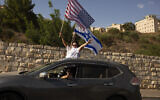 Supporters of US President Donald Trump's re-election wave an American and an Israeli flag from a car headed for a rally outside of the US Embassy in Jerusalem, October 27, 2020. (Maya Alleruzzo/AP)