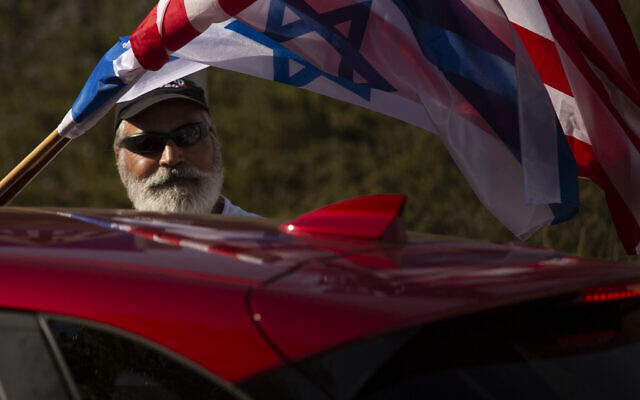 An Israeli supporter of the reelection of US President Donald Trump waves American and Israeli flags from a car at a rally outside of the US Embassy, in Jerusalem, Tuesday, Oct. 27, 2020. (AP Photo/Maya Alleruzzo)