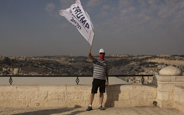 An Israeli supporter of US President Donald Trump waves a campaign flag at a rally for his re-election, on a promenade overlooking Jerusalem, October 27, 2020. (Maya Alleruzzo/AP)