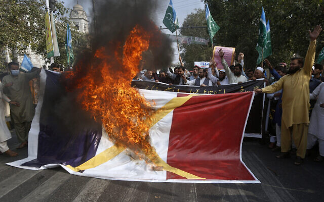 Supporters of religious groups burn a representation of a French flag during a rally against French President Emmanuel Macron and the republishing of caricatures of the Prophet Muhammad they deem blasphemous, in Lahore, Pakistan, Oct. 30, 2020. (AP Photo/K.M. Chaudary)