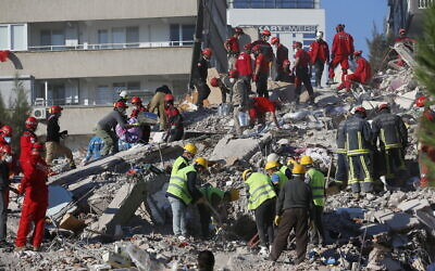 Members of rescue services search for survivors in the debris of a collapsed building in Izmir, Turkey, October 31, 2020. (AP Photo/Darko Bandic)
