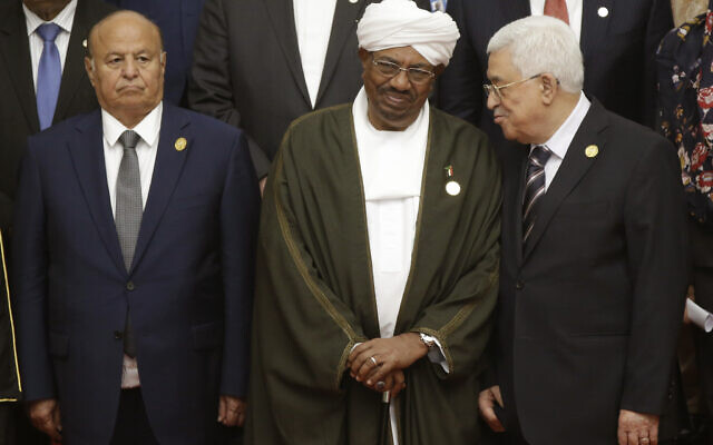 Former Sudanese President Omar al Bashir, center, confers with Palestinian Authority President Mahmoud Abbas, right, as Yemen's President Abdo Rabbo Mansour Hadi looks on as they prepare for a photo session at the extraordinary Organization of Islamic Cooperation (OIC) summit on Palestinian issues in Jakarta, Indonesia, Monday, March 7, 2016. (AP Photo/Dita Alangkara)