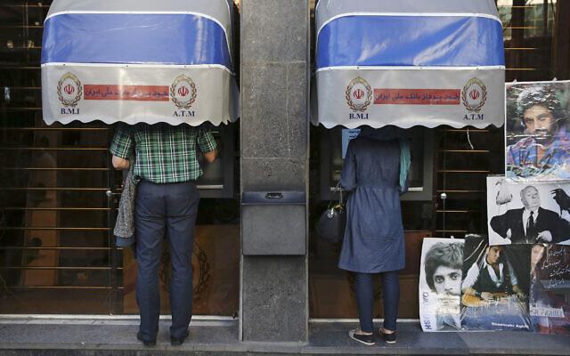 Iranians use ATMs of Bank Melli Iran in downtown Tehran, Iran, April 4, 2015. (AP Photo/Vahid Salemi, File)
