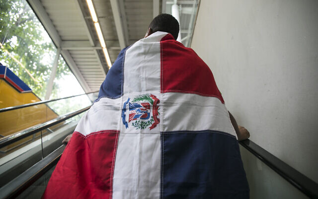 Illustrative: A man wears a Dominican flag on his way out of the subway station to march with the Green Movement in Santo Domingo, Dominican Republic, July 16, 2017. (AP Photo/Tatiana Fernandez)