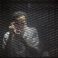 Illustrative: In this July 28, 2018 file photo, Egyptian photojournalist Mahmoud Abu Zied, known by his nickname Shawkan, gestures in a soundproof glass cage inside a makeshift courtroom in Tora prison in Cairo. (AP/Amr Nabil, File)