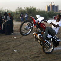 A Sudanese man performs on his motorbike on the bank of Nile River, in Khartoum, Sudan, Friday, June 21, 2019.   (AP/Hussein Malla)