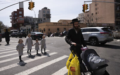 Illustrative: An ultra-Orthodox Jewish man walks with his daughters in the Williamsburg neighborhood of Brooklyn, Tuesday, April 7, 2020 (AP Photo/Mark Lennihan)
