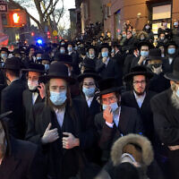 "Hundreds of mourners gather in the Brooklyn borough of New York, Tuesday, April 28, 2020, to observe a funeral for Rabbi Chaim Mertz, a Hasidic Orthodox leader whose death was reportedly tied to the coronavirus. The stress of the coronavirus' toll on New York City's Orthodox Jews was brought to the fore on Wednesday after Mayor Bill de Blasio chastised ""the Jewish community"" following the breakup of the large funeral that flouted public health orders.(Peter Gerber via AP)"