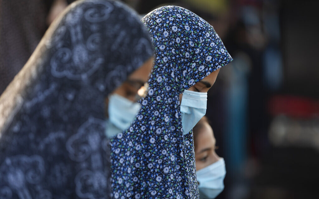 Muslim worshippers wearing face masks offer Eid al-Adha prayer at a park as mosques are limited for ten people following the government's measures to help stop the spread of the coronavirus, in the mixed Arab Jewish city of Jaffa, near Tel Aviv, Israel, Friday, July 31, 2020. (AP Photo/Oded Balilty)