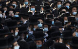 Haredi Jews from the Hasidic sect of Shomrei Emunim attend the funeral of Rabbi Refael Aharon Roth, 72, who died from the coronavirus, in Bnei Brak, Israel, August 13, 2020. (AP Photo/Oded Balilty)